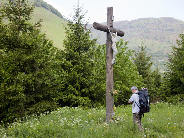 A pilgrim prays before a crucifix in Somport, France, along the Way of St. James. Last year, nearly 200,000 pilgrims walked the journey.