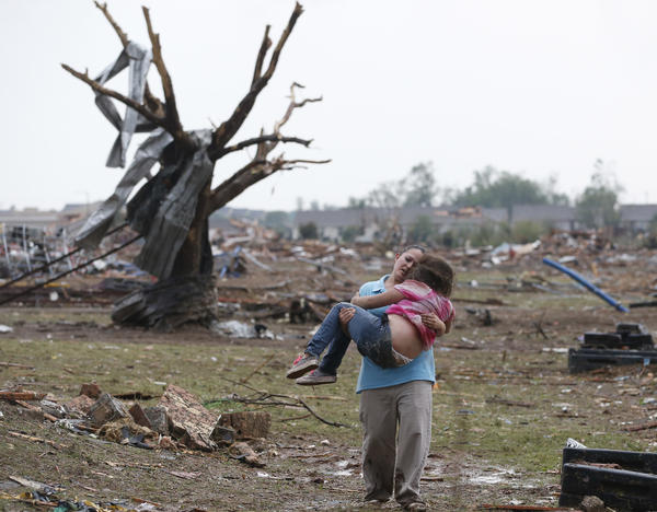 A woman carries her child through a field near the collapsed Plaza Towers Elementary School in Moore, Okla., on Monday A tornado as much as a mile wide with winds up to 200 mph roared through the Oklahoma City suburbs flattening entire neighborhoods, setting buildings on fire and landing a direct blow on an elementary school.