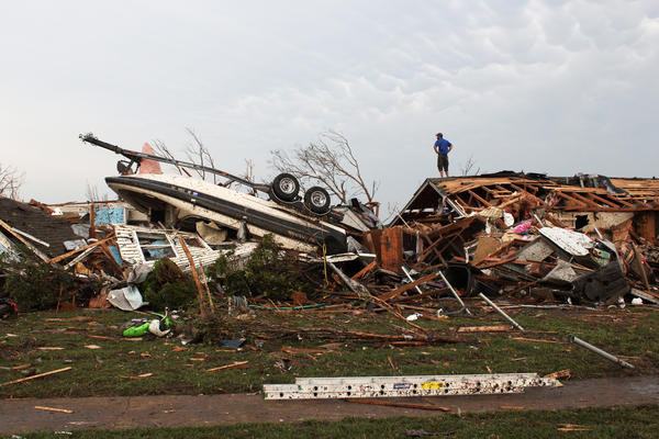 A man surveys tornado damage from a roof in Moore, Okla., on Monday. The death toll from the massive twister is expected to rise.
