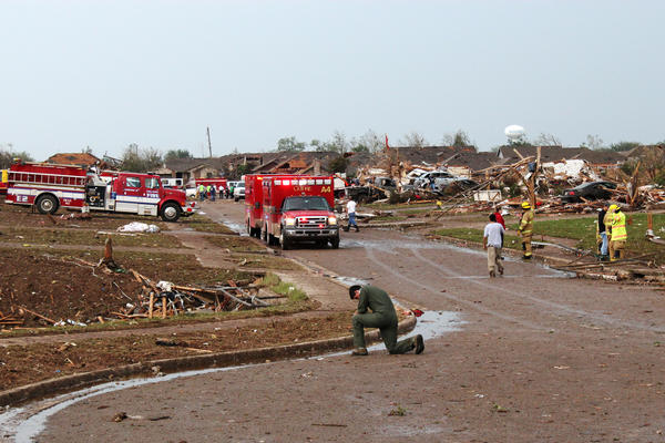 An airman kneels and prays in the Moore neighborhood south of Plaza Towers Elementary School.