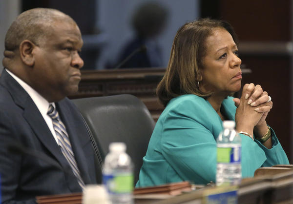 Chicago Public Schools CEO Barbara Byrd-Bennett and Board of Education General Counsel James Bebley listen at a packed board meeting Wednesday in Chicago. The board voted Wednesday on Mayor Rahm Emanuel's proposal to close dozens of schools.