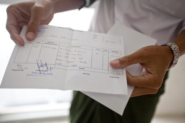 One of Aung's employees holds up the receipt of a payment he is about to deliver to one of Aung's partner hotels. Even though Aung enables tourists to handle their travel bookings online, he still has to deliver cash to his partners by hand.