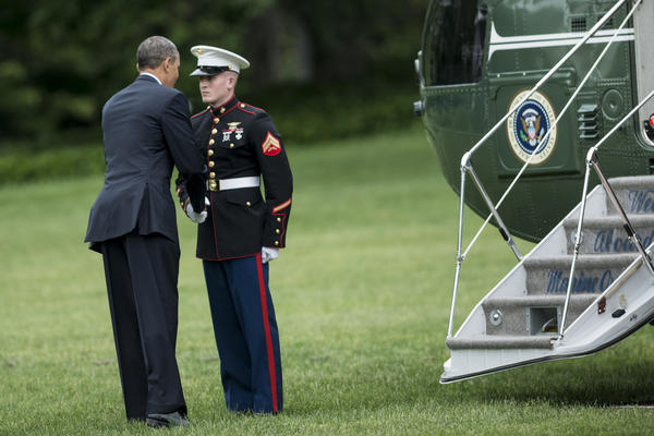 President Obama greets a Marine after forgetting to salute him while boarding Marine One on the South Lawn of the White House.