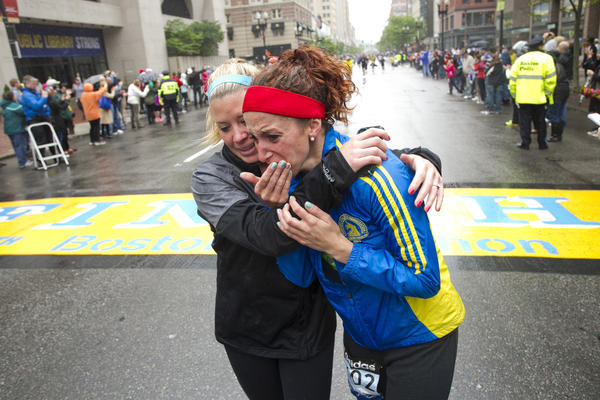 "Erin Roy, left, comforts Elise Wulff as runners cross the finish line after completing the final mile of the Boston Marathon course during ""#onerun"" in Boston, Massachusetts, on Saturday."