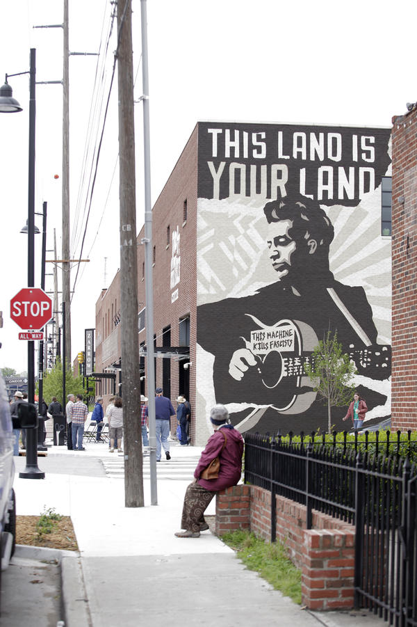 """Outside the Woody Guthrie Center, there's a large mural of Guthrie holding his guitar bearing the phrase, """"This Machine Kills Fascists."""""""