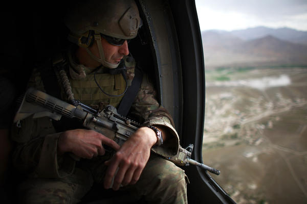 Lt. Col. Brad Moses looks out the window of his helicopter while flying south of Kabul. Moses commands all U.S. Army Green Beret teams in eastern Afghanistan. The teams are attempting to shore up security before American forces withdraw.