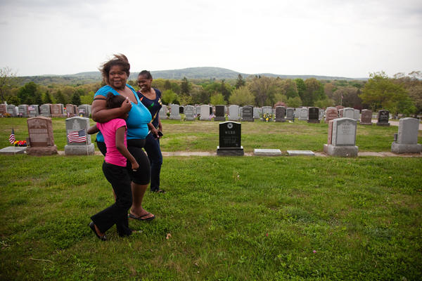 Michelle Williams (center) and two daughters visit the grave of her mother, Judy Williams, at Fairview Cemetery in Hyde Park, Mass., on May 11. Judy died in 2011.