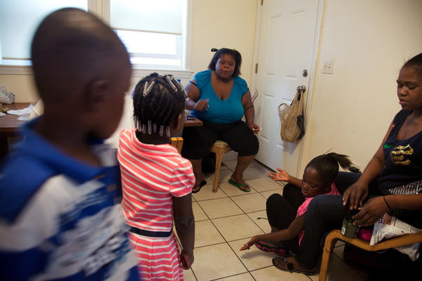 "Michelle Williams (center), at home in Dorchester, Mass., talks with grandchildren Ayniah Williams (pink dress) and Drequain Smith (far left). At right are her daughters Vanessa ""Nessa"" Williams (far right) and Margaret Williams. Both Michelle and Ayniah had latent TB infections and have been treated."