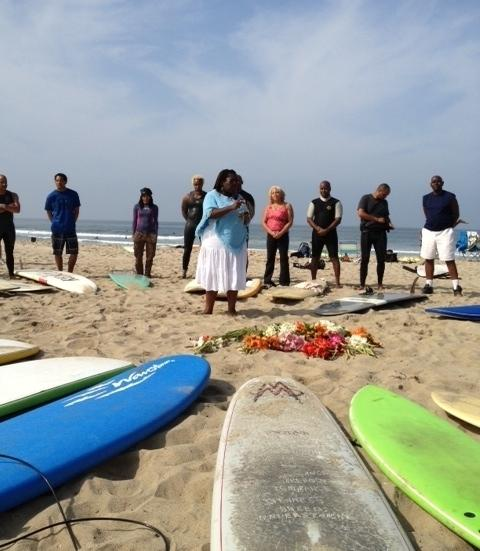 Surfers surround a celebrant who pours libations and says prayers to honor the spirit of surfers past and present and to give thanks to the sea for providing sustenance and recreation.