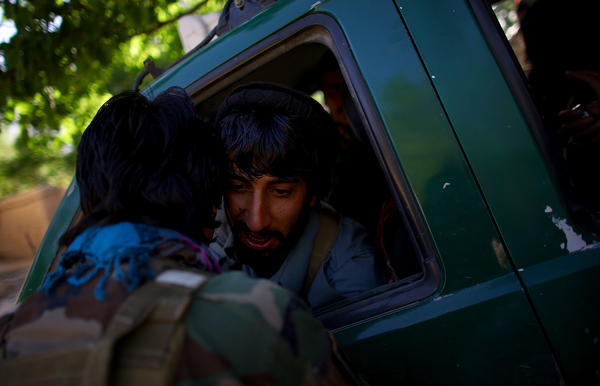 An ANASF soldier talks with a regular army soldier while on a patrol in the village of Kasan.