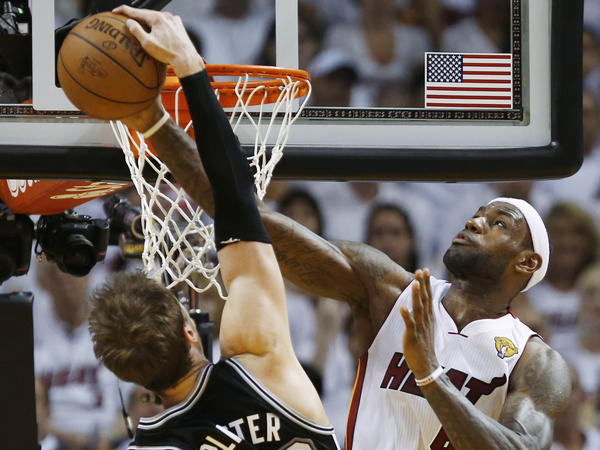 Oh no you don't: The Miami Heat's LeBron James (right) rejects a slam dunk attempt by the San Antonio Spurs' Tiago Splitter during Sunday night's game in Miami.