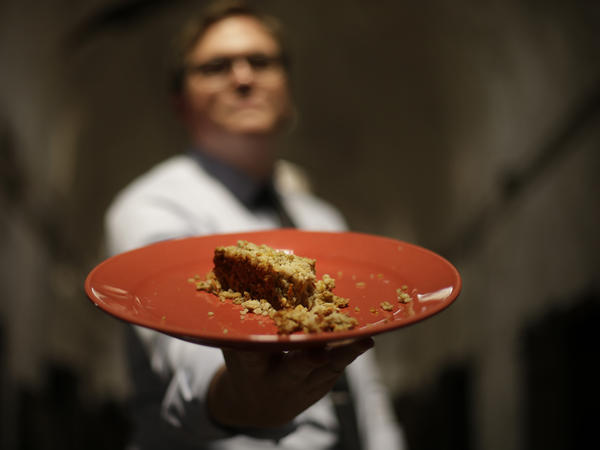 "Sean Kelley, senior vice president at the Eastern State Penitentiary, displays a plate of ""food loaf,"" a punishment food currently served in Pennsylvania prisons. Over the weekend, the historic penitentiary, now a museum, served visitors sample meals from the 1800s, 1900s and today."