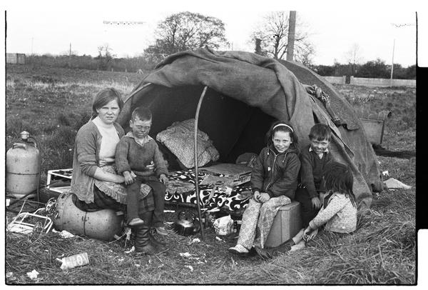 A group of Irish Travelers stand outside a traditional canvas tent in Lisburn, Northern Ireland, 1972.