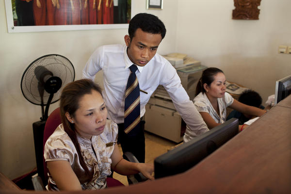 Hotel employees, including Yin Sochen (center), work behind the reception desk at the Soria Moria. The employees were resistant to the idea of owning the hotel at first but have since embraced the responsibility.
