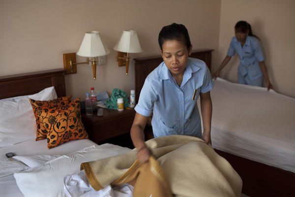 Srey Tol (left) and another employee clean a room at the hotel. All 29 full-time employees co-own the Soria Moria.