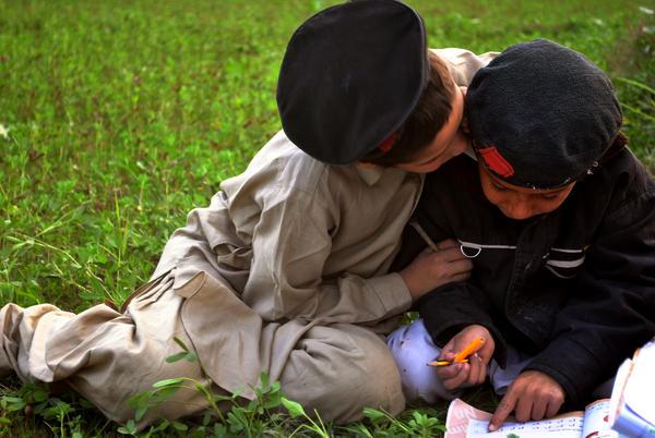 Children work on their homework after school in a village near Peshawar.