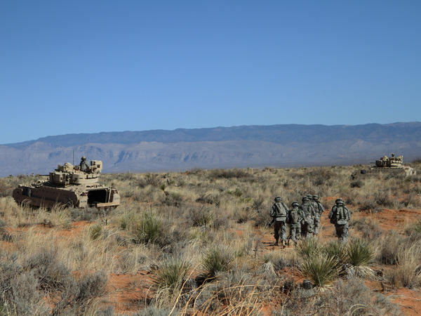 Soldiers approach armored vehicles after a training exercise at Fort Bliss, Texas, in January.