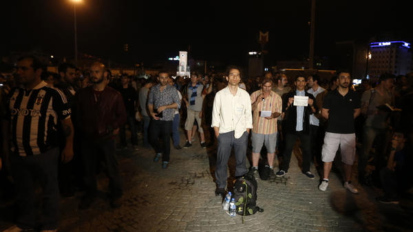 Erdem Gunduz (center) stands in Instanbul's Taksim Square early Tuesday. After weeks of clashes with police, many Turkish protesters were  inspired to emulate Gunduz, and stand silently.