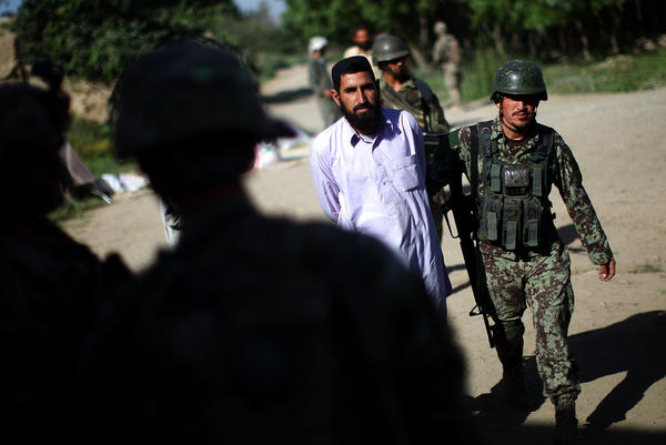 An Afghan Army soldier brings in a local farmer the Americans wanted detained. The American soldiers later handed the man back to the Afghans, who eventually let him go. The incident stoked both anger and fear among local residents.