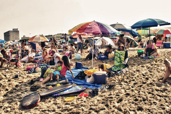 Lazy day summer beach goers relax on the sands of Rehoboth Beach in Delaware.