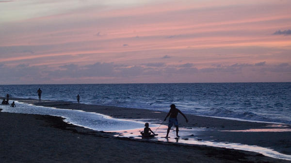 Children play on a beach in San Juan, Puerto Rico. The Puerto Rican government hopes that convincing wealthy investors to relocate here will boost the island's economy.