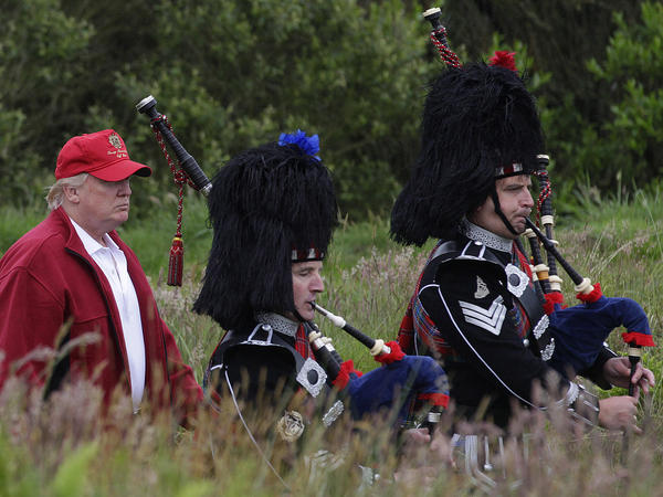 Trump, left, follows bagpipers to the opening of his Trump International Golf Links golf course near Aberdeen, northeast Scotland, last July.