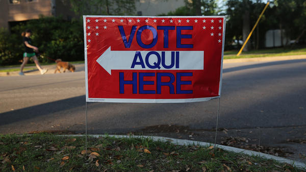 A bilingual sign stands outside a polling center at a public library ahead of local elections on April 28 in Austin, Texas.