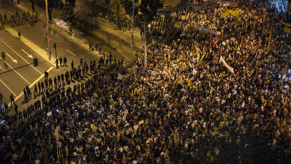 """Protesters gather near a line of security blocking a road that leads to Maracana stadium in Rio de Janeiro, Brazil, on Sunday. <a href=""""http://n.pr/19Y62Yz"""">Anti-government protesters</a> marched near the soccer stadium before a major international match, venting their anger about the billions of dollars the government is spending on major sporting events rather than on public services."""