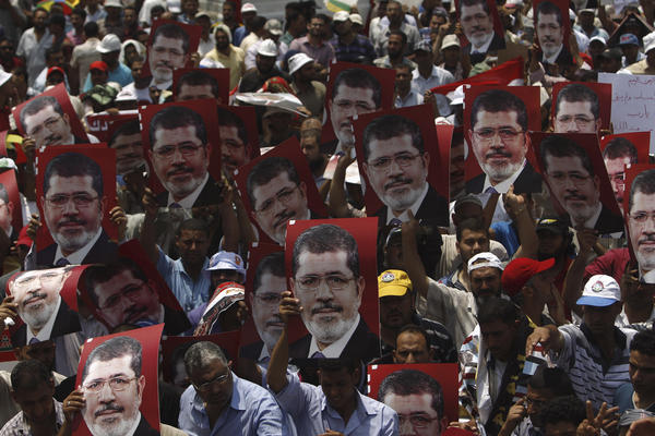 Supporters hold up posters of Morsi during a rally at the Raba El-Adwyia mosque square in Cairo.
