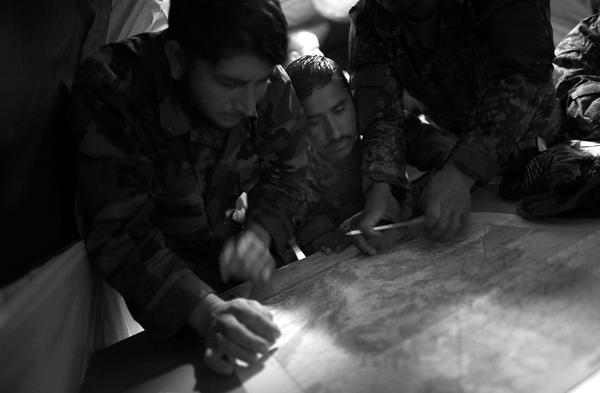 ANA soldiers plot coordinates on a map with the help of their American trainers.
