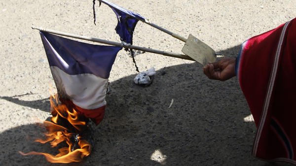 A man burns the French flag outside France's embassy in La Paz, Bolivia, Wednesday. Bolivia's President Evo Morales is returning home late today, after his plane was not allowed to fly in the airspace of France and other countries.