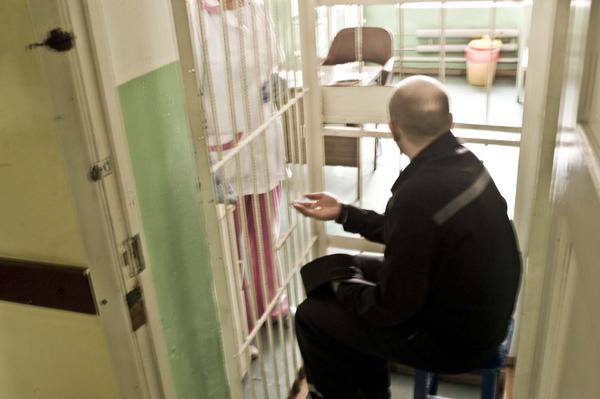 An inmate takes anti-TB medication inside his cell.