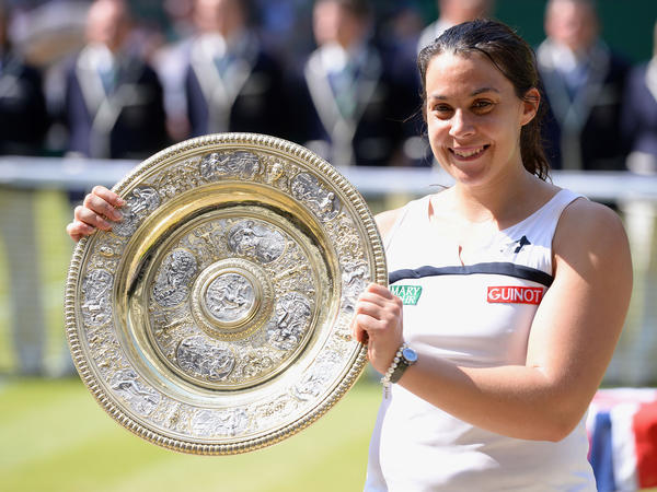 France's Marion Bartoli celebrates her women's singles championship at The All England Lawn Tennis and Croquet Club in Wimbledon.