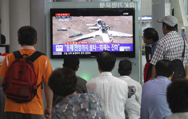 "People watch a news program reporting on the accident at Seoul Railway Station in South Korea. The writing on the screen reads, ""Fire on the ceiling of the airplane."""