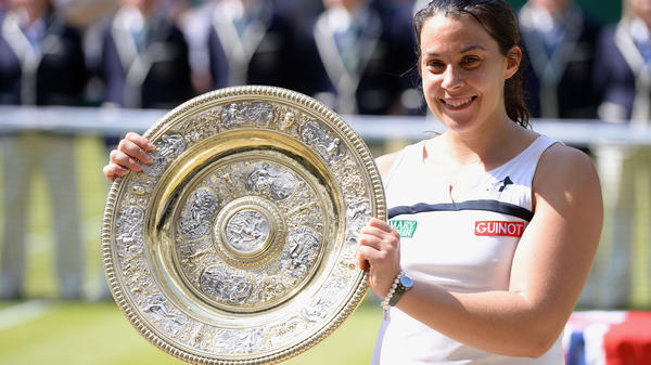 France's Marion Bartoli celebrates her Wimbledon women's singles championship. The BBC has apologized to Bartoli for remarks an announcer made about her appearance.