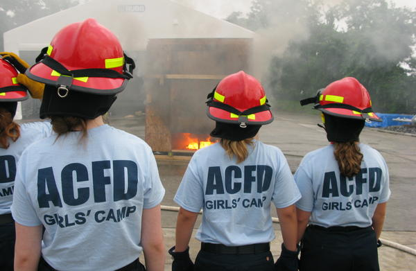 Girls at the Arlington County, Va., fire camp watch a staged fire. Firefighters hope to encourage the teenagers to consider the fire service as a career.