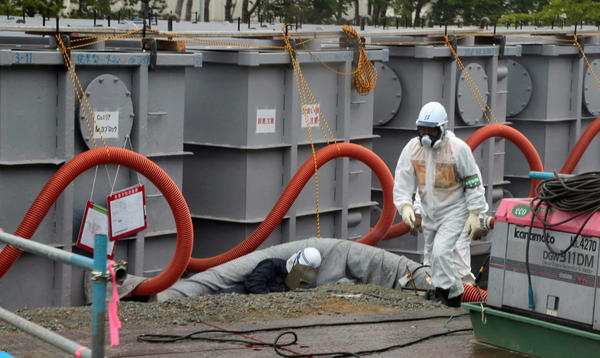 Tokyo Electric Power Co (TEPCO) workers work on waste water tanks at Japan's Fukushima Daiichi nuclear plant in the town of Okuma, Fukushima prefecture in Japan on June 12, 2013.