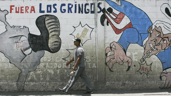 """A man walks past anti-U.S. graffiti that reads """"Gringos out"""" in Spanish."""