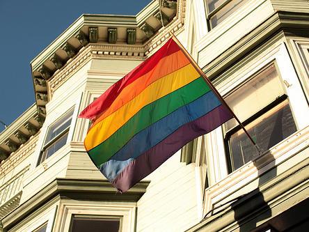 A rainbow flag against a San Francisco roofline.