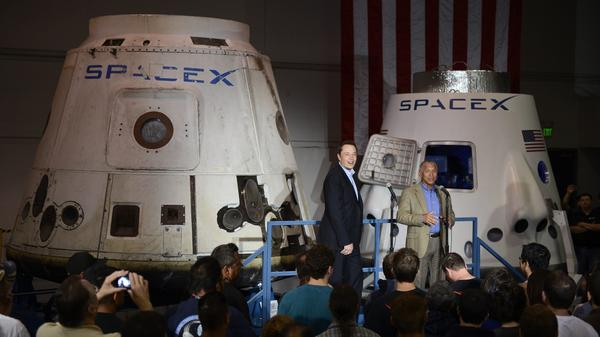 Elon Musk (left) and NASA Administrator Charles Bolden talk to employees at the SpaceX headquarters, with the DragonRider spacecraft capsule behind them, in Hawthorne, Calif., in 2012.