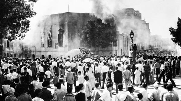 Crowds gather around the burning headquarters of the Muslim Brotherhood in Cairo on Oct. 27, 1954. The building was set on fire following the attempted assassination of President Gamal Abdel Nasser.
