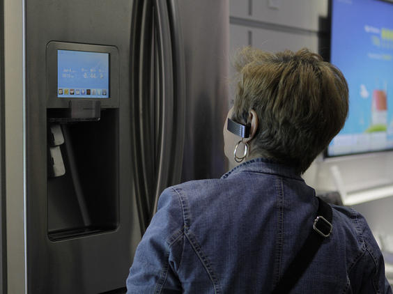 A woman checks out a smart refrigerator at a consumer electronics show in 2012.