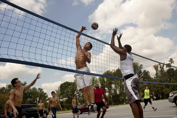 "Team co-captain Ceril Venegas, 17, (center) takes the ball over the net against Gerel Hall, 20, who practices with the Youngbloods. ""Usually [players] are smart enough not to dive"" onto the asphalt or concrete 9-man court, Venegas says."