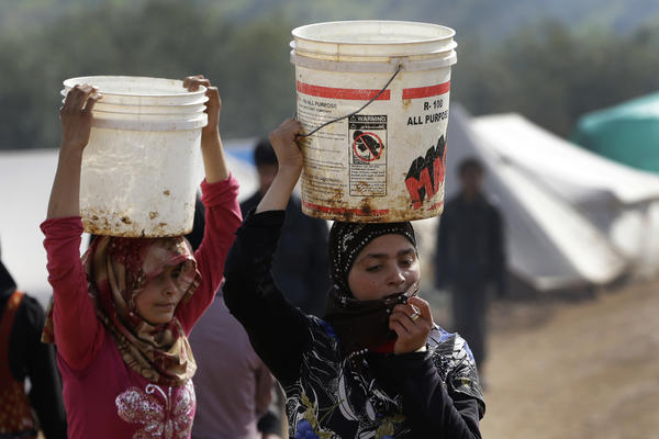 Girls carry over their heads buckets of water as they walk at Atmeh refugee camp, in the northern Syrian province of Idlib on Feb. 19. This rebel-controlled camp only yards from the border with Turkey houses some 16,000 people displaced by the civil war.