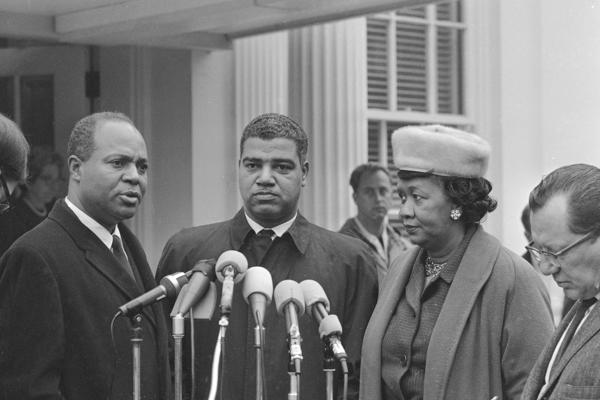 Three of the six leaders of African-American organizations who met with President Lyndon B. Johnson Nov. 19, 1964, talk with reporters at the White House after the meeting. They are, left to right: James Farmer, national director of the Congress of Racial Equality; Whitney M. Young, Jr., executive director of the National Urban League; and Dorothy Height of the National Council of Negro Women.