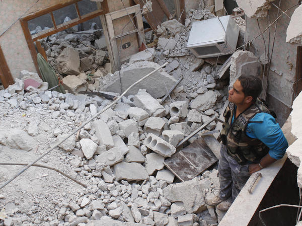 In Aleppo, Syria, on Monday, this Free Syrian Army fighter stood in the rubble of a building that has collapsed during fighting there.