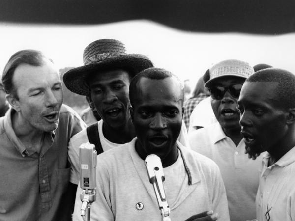 "American folk singer and activist Pete Seeger (left) adopted and helped popularize ""We Shall Overcome"" by teaching the song at rallies and protests. Here he sings with activists in Greenwood, Miss., in 1963."