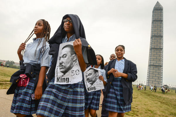 Dupont Park Seventh Day Adventists students carry posters of King as they pass the Washington Monument.