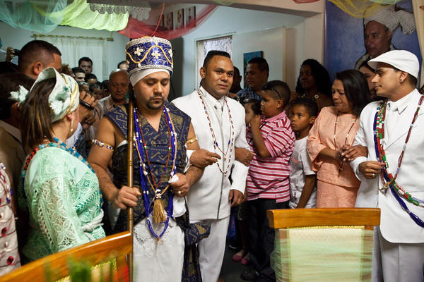 At a Candomblé wedding ceremony in Sao Paulo, the groom, William de Souza Santos, enters the room accompanied by the deity Toy Dou, who represents iron.