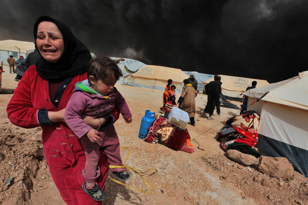 A woman carries her child to escape from the burnt tents at Zattari Syrian refugee camp near Mafraq, Syria, on March 8. A heavy fire broke out and consumed a large number of tents. UNICEF reports that more than two million Syrian children are internally displaced refugees within Syria.